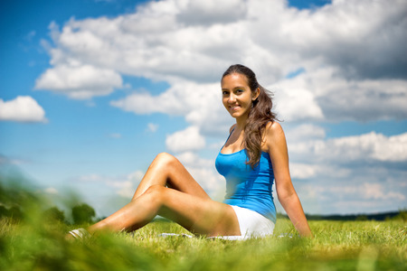 Smiling friendly beautiful young teenage girl sitting on the green grass in a field enjoying the summer sunshine, low angle view against a beautiful cloudy blue sky photo