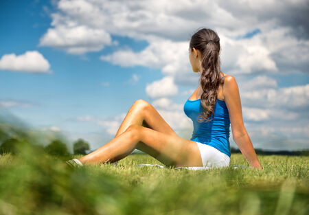 looking towards camera: Tanned slender woman sitting in the grass in a green field looking away from the camera with her long brunette hair in a ponytail towards a sunny cloudy blue summer sky