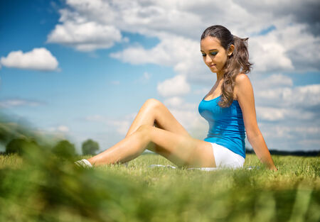 sexy shorts: Beautiful slender tanned leggy young girl in shorts sitting relaxing in a green field in the warm summer sunshine, low angle view under a blue sky with fluffy white clouds Stock Photo