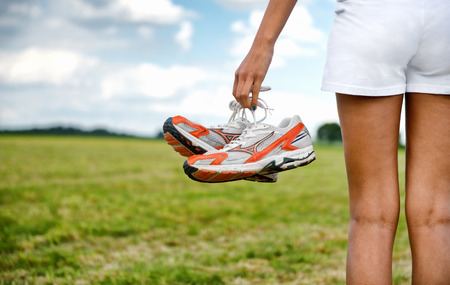 running pants: Young girl in shorts holding her sneakers in her hand as she stands looking out over a rural field, close up view of the shoes from behind
