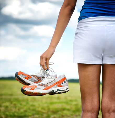 Young girl in shorts holding her sneakers in her hand as she stands looking out over a rural field, close up view of the shoes from behind