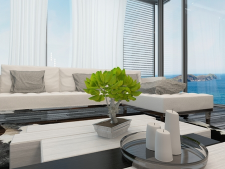 Modern bright airy living room or lounge interior overlooking the sea with large view windows with curtains and blinds, a modern upholstered lounge suite and a bonsai on the table photo