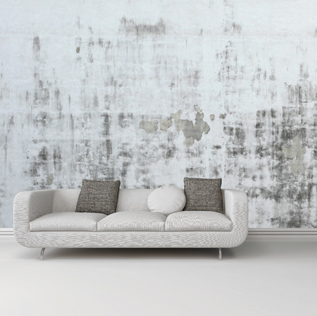 sitting room: Greyscale image of an upholstered white sofa against an abstract wall with a grunge rustic pattern over a plain white floor with skirting board Stock Photo