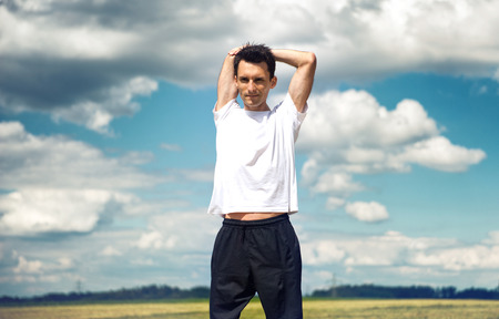 arms behind head: Man stretching his muscles before training standing against a cloudy blue sky in the countryside with his arms raised behind his head as he begins exercising