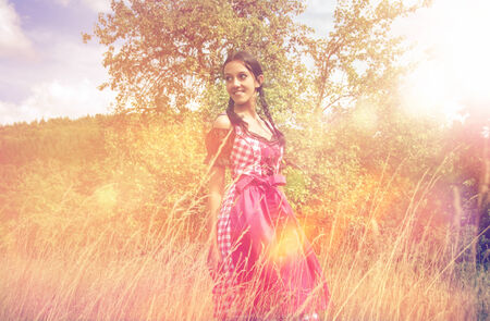 Young woman in traditional Bavarian dirndl walking alone in the field photo