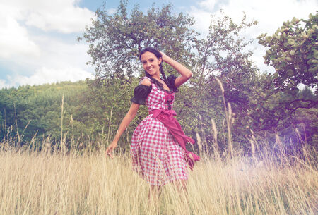 Young woman wearing a Bavarian dirndl posing in the field photo