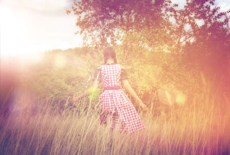 dirndl: Rear view of young woman in Bavarian dirndl walking alone in the field
