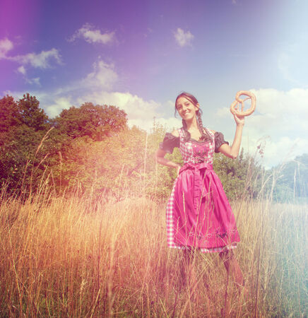 dirndl dress: Bavarian girl wears a traditional dirndl and holds a brezel