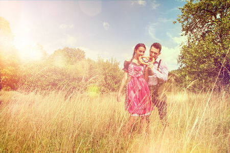 dirndl: Loving couple in traditional Bavarian Dirndl and Lederhosen eat a brezel outside Stock Photo