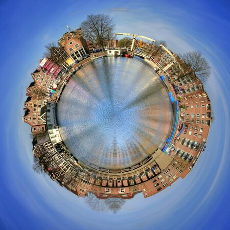 circumference: 360 degree view of Amsterdam canal houses around the circumference of a watery planet with reflections and winter trees, floating in a blue sky