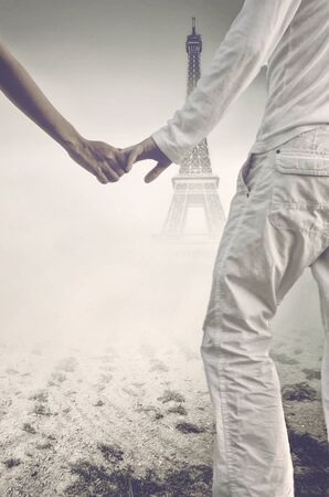 sweethearts: Sweethearts in love holding hands in front of the Eiffel Tower, Paris, viewed through a misty with toned effect conceptual of romance, honeymoon, tourism or travel