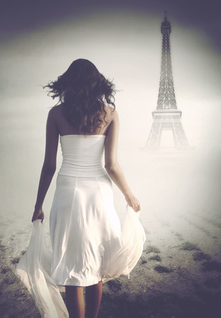 Artistic rear view of a brunette mysterious woman wearing white long skirt, top and holding a veil while walking towards the Eiffel Tower, in a misty atmosphere, in Paris, France