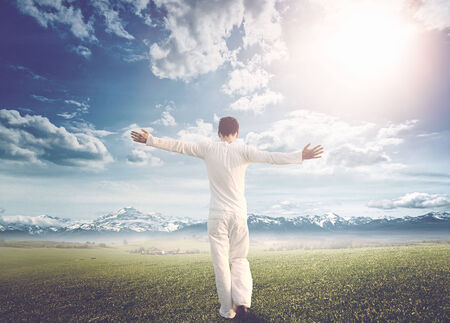 自由の概念は、劇的な明るい晴れた空の下、雪をかぶった山の範囲に向かって緑の広い草原を歩いて服を着て白い夏、両腕を広げて、男の背面図