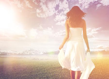 Svelte cheveux longs femme portant robe blanche d'été tout en marchant sur une verte prairie vers un horizon lumineux et ensoleillé, sous un ciel dramatique, tir de derrière, en haute clé
