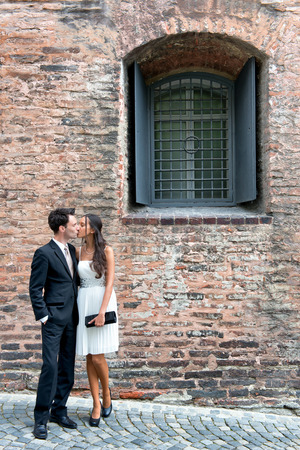 Loving stylish young couple standing in an intimate embrace on a cobbled street outside an old brick building photo
