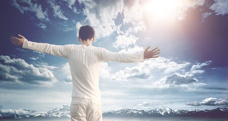 outspread: Man celebrating nature and his freedom standing with his back to the camera with wide outspread arms against a blue cloudy sky over snowy mountains with a bright sunburst and lens flare