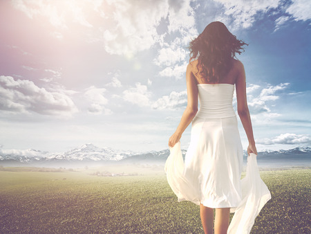Slender long-haired woman wearing white summer dress while walking on a green meadow towards a bright and sunny horizon, shot from behind