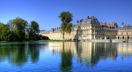 View of the Chateau de Fontainebleau and its reflection across a tranquil lake, situated close to Paris it introduced the Mannerist style of architecture to France and is the largest royal chateau