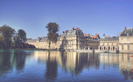 ile de france: View of the Chateau de Fontainbleu and its reflection across a tranquil lake, situated close to Paris it introduced the Mannerist style of architecture to France and is the largest royal chateau