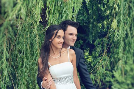 they are watching: Romantic fashionable young couple under a weeping willow holding each other close as they stand watching something off frame to the right with happy smiles Stock Photo