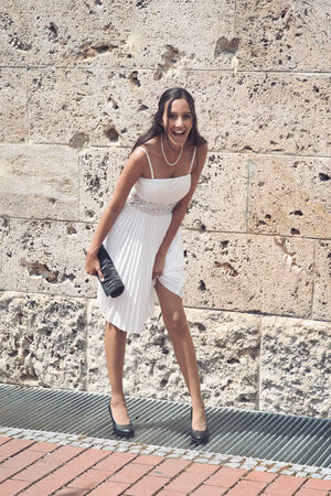 mirth: Candid image of a laughing vivacious elegant young woman in a white summer dress and high heels carrying a clutch purse standing in front of an old stone building Stock Photo