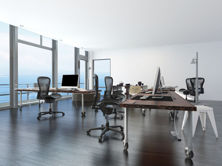 Modern minimalist office with computer work stations on wheeled tables in a spacious open plan room overlooking the sea photo