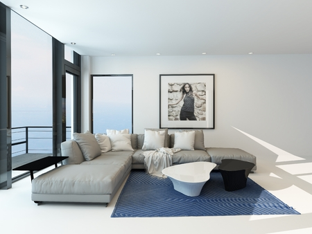 couch: Modern waterfront living room with a bright airy lounge interior with a comfortable modern upholstered grey suite , art on the wall and a large panoramic view window along one wall overlooking the ocean