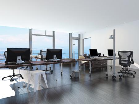 Bureau de front de mer moderne avec vue sur la mer avec plusieurs postes de travail informatiques sur mobiles tables de bureau à roulettes dans une pièce lumineuse et aérée avec une fenêtre de vue en verre ou mur