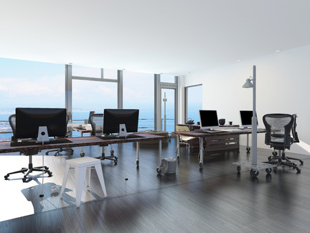 uncarpeted: Modern waterfront office overlooking the sea with several computer workstations on movable wheeled office tables in a bright airy room with a glass view window or wall Stock Photo