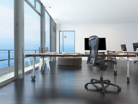 balcony design: Modern waterfront office overlooking the sea with several computer workstations on movable wheeled office tables in a bright airy room with a glass view window or wall Stock Photo