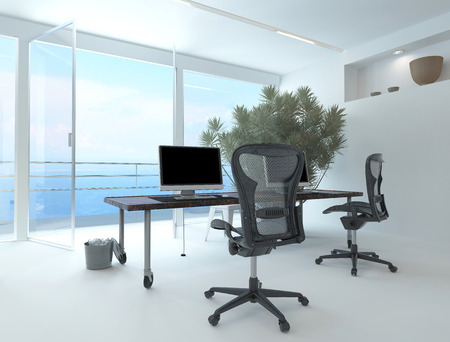 Modern waterfront office interior with a computer workstation and chairs in front of a large floor-to-ceiling glass window overlooking the sea and a large potted plant in the corner Stock Photo