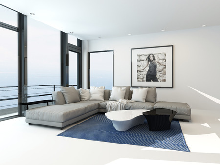 Modern waterfront apartment interior with an upholstered grey corner lounge suite in front of floor-to-ceiling glass windows overlooking the ocean