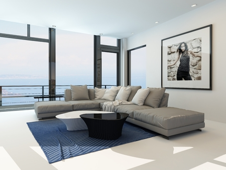 suite: Modern waterfront living room with a bright airy lounge interior with a comfortable modern upholstered grey suite , art on the wall and a large panoramic view window along one wall overlooking the ocean