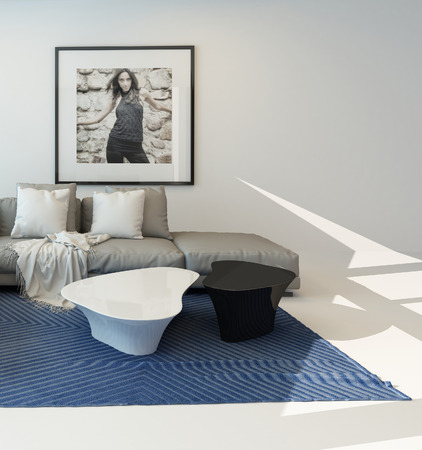 Modern living room with a bright airy lounge interior with a comfortable modern upholstered grey suite and art on the wall