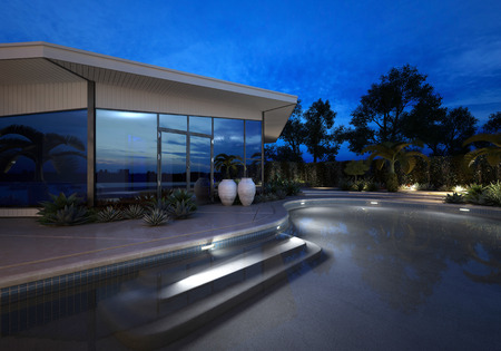 exterior wall: Luxury modern villa or house with large plate glass windows at night with an illuminated curving swimming pool surrounded by potted tropical plants and palms Stock Photo