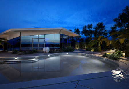 Luxury house with a landscaped swimming pool with a paved surround and potted tropical plants and palm trees viewed at night with the shimmering tranquil water illuminated