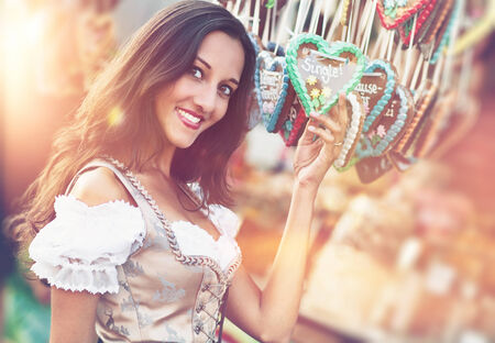 Young beautiful woman in Dirndl costume together with German Gingerbread heart photo