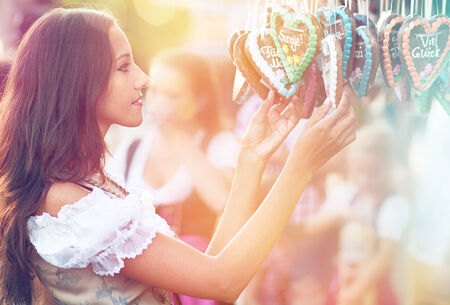dirndl: Young beautiful woman in Dirndl costume together with German Gingerbread heart