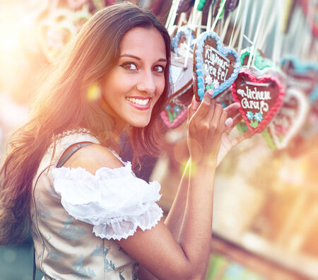 charismatic: Young beautiful woman in Dirndl costume together with German Gingerbread heart