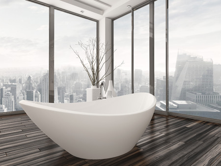 Modern bathroom interior with a freestanding white bathtub on a natural wood parquet floor in front of floor-to-ceiling glass windows overlooking a town Stock Photo
