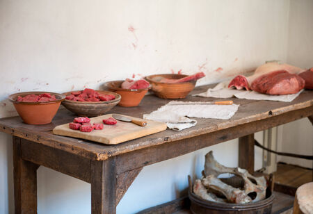 meat counter: Uncooked red meat in bowls and displayed on a wooden chopping board on a rustic kitchen counter with old fashioned knives and cloths Stock Photo
