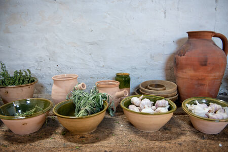 flavorings: Fresh herbs and garlic displayed in earthenware bowls on an old rustic kitchen counter ready to be used as seasoning and flavoring in cooking