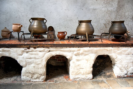 Display Of Old Earthenware And Iron Cooking Pots On An Old Kitchen Range  With Arched Stone