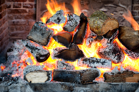 incendiary: Glowing coals in a wood fire with fiery orange flames in a brick hearth or fireplace with a wrought iron backplate, close up backgroud view