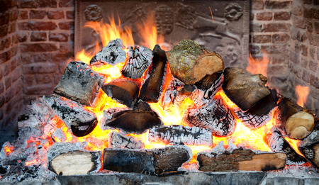 the backplate: Glowing coals in a wood fire with fiery orange flames in a brick hearth or fireplace with a wrought iron backplate, close up backgroud view