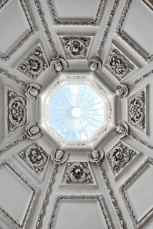 glimpse: Looking up into a domed roof with a skylight at the top where all the ornate panels with their relief carvings converge with a glimpse of blue sky, architectural background Editorial