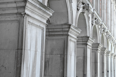 architectural styles: Architectural background of a row of classical rectangular columns in a colonnade supporting a row of arches, receding perspective Stock Photo