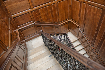 handrail: Winding interior staircase with wood paneling on the walls and an ornate wrought iron and oak bannister viewed looking down the treads from above Editorial