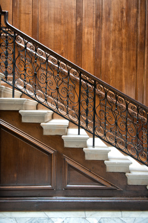 Flight of old ornate interior stairs with a decorative wrought iron bannister and wood paneling on the walls, view from the side photo