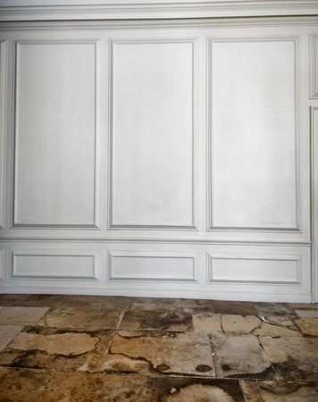White wooden paneling above a cracked, weathered and worn old flagstone floor in an architectural background photo